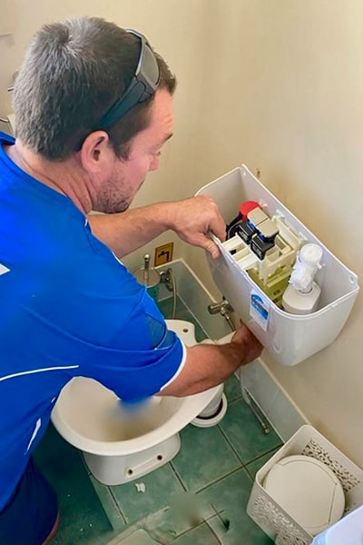 Unclogging toilet by a plumber in Redcliffe