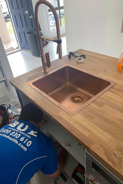 Plumber in Redcliffe changing the pipes on a kitchen counter